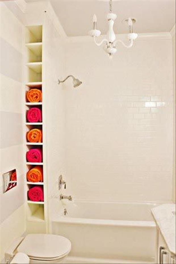 Towel storage in the bathroom – Shelf for towels, on the wall, by the tub. Small bathroom organization. I think it would be cool to paint the inside of the shelf lime green with pink towels.