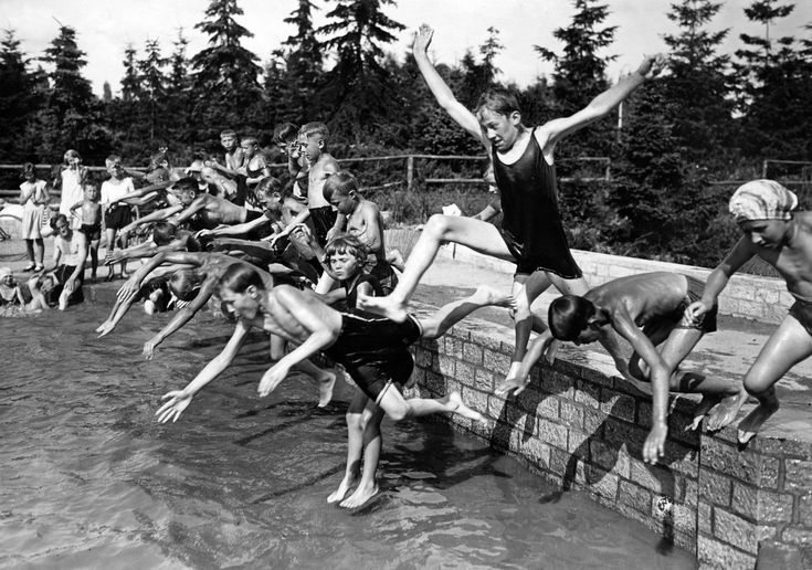 23 Vintage Photos That Show What Summer Fun Looked Like Before The Internet --- Summer delight at outside temperatures of 30 degrees celsius in Berlin: children jump into a pool in the Volkspark (urban park) of Berlin-Mariendorf - 1932 - Published by: 'Berliner Morgenpost' 26.07. (Photo by bpk/Willy Römer/ullstein bild via Getty Images)