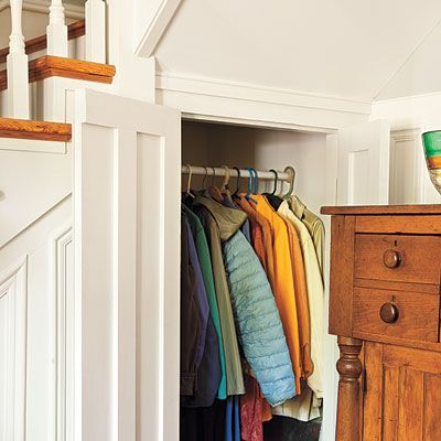 Recessed panels under a front-hall staircase conceal a coat close. | Photo: Deborah Whitlaw Llewellyn | thisoldhouse.com