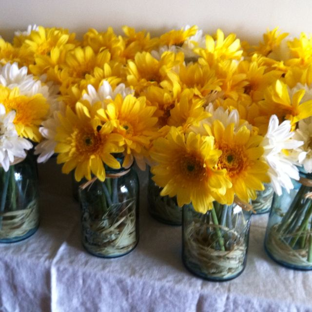 Blue mason jars with raffia and white and yellow daisies...our wedding centerpieces