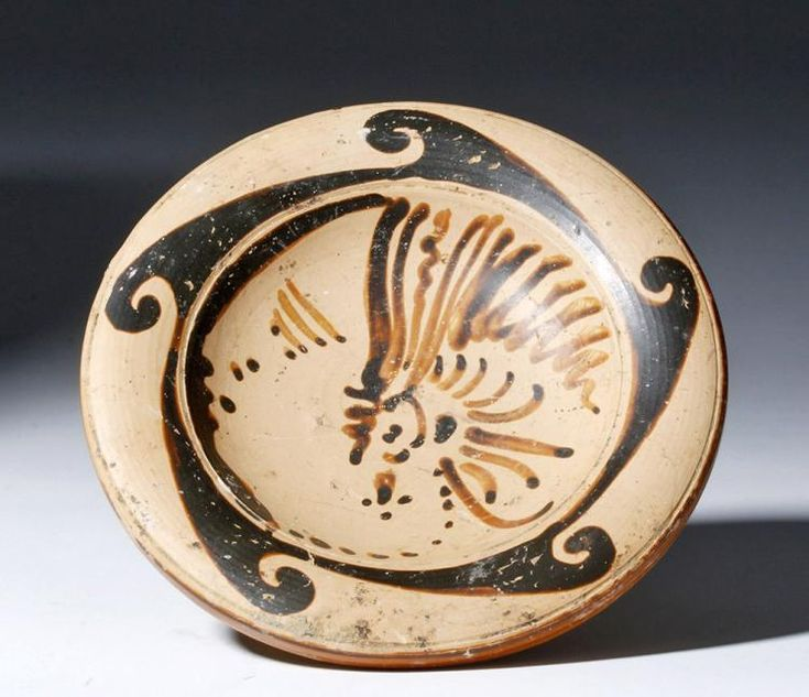 """Northern Italy, Etruria, 4th century BCE. Lovely and well-preserved pottery pedestal plate from the very important Genucilia group of painters. Portrait in profile facing left, 5-band wave around, ringed decoration on underside of plate. The vast majority of plates in the Genucilia style are simple geometric patterns. This is a very fine example with finely painted profile! Size: 5.5"""" W x 2.125"""" H (14 cm x 5.4 cm) <BR><BR> Provenance: Ex- Michael Reiniger collection, Chicago, IL acquired…"""