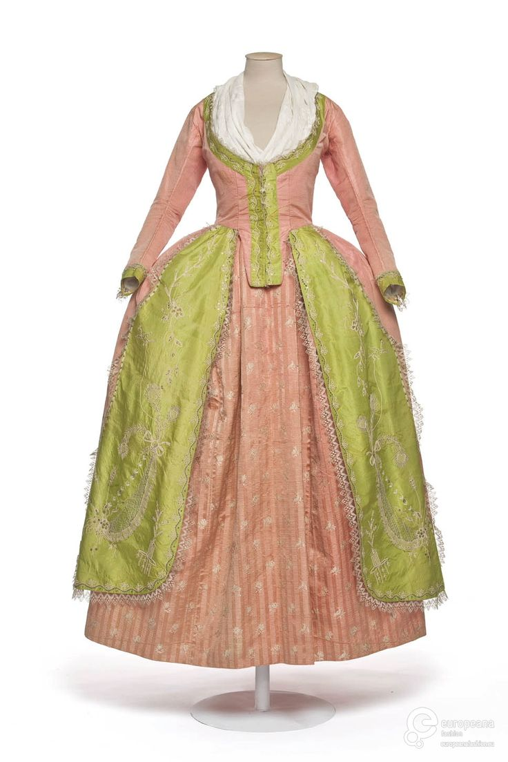 Robe à la polonaise, 1780-1785. Manteau of pink and green silk, embroidered with floral motifs in white silk and sequins, lace trimming, petticoat of pink striped silk, embroidered with white floral sprays.