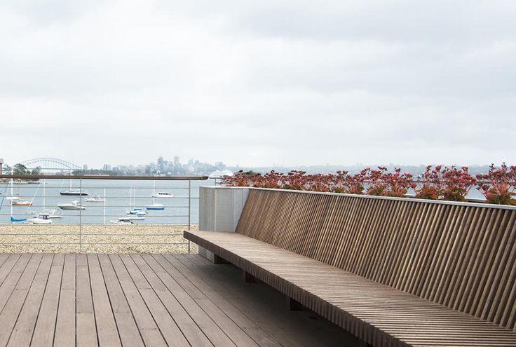 VILLA SULLA BAIA DI SYDNEY - IL PANORAMA Il terrazzo, con vista sulla baia, è rivestito da un deck in legno e arredato con una panca a doghe. In lontananza si intravedono i grattacieli che caratterizzano lo skyline di Sydney.