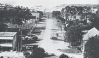 "A view from Southern College. Looking down unpaved Florida Avenue out over Sutherland bayou, with the Gulf beyond, one may see the wooden sidewalk on which students could walk all the way out to Pig Island for picnics and ""surf bathing."" Originally, the means of transportation down to the dock was a mule-drawn ""bob-tailed streetcar."" The buildings in the foreground survive as two of the last remaining structures from Palm Harbor's early days.  Courtesy of the Wallace Collection."