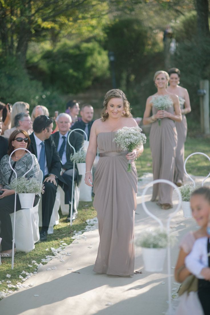 Bridesmaids looking gorgeous in their long dresses with baby's breath bouquets