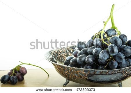 Antique fruit bowl with cluster of grapes, on wooden surface with white…