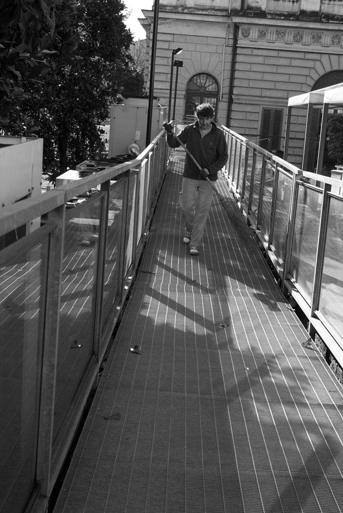 Giovanni pulisce una passarella dalle foglie dopo una potatura alla facoltà di Fisica dell'Università degli studi di Torino. www.coopagridea.org