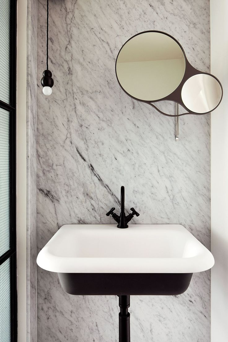 "Carrara stone is used extensively throughout the home, especially in the downstairs powder-room as a full wall slab outfitted with a monochrome [Agape](http://www.agapedesign.it/en/bathrooms/|target=""_blank"") sink and mirror."