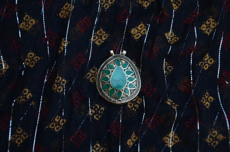 "This silver plated and green stone pendant was purchased in Istanbul. It is  1.75"" tall and almost 1.5"" wide.  It is the perfect addition to any wardrobe! This item does not come with a chain."