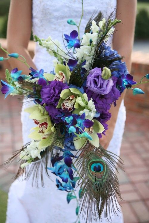 Peacock feather embellished bridal bouquet with purple, blue, turquoise and cream flowers.
