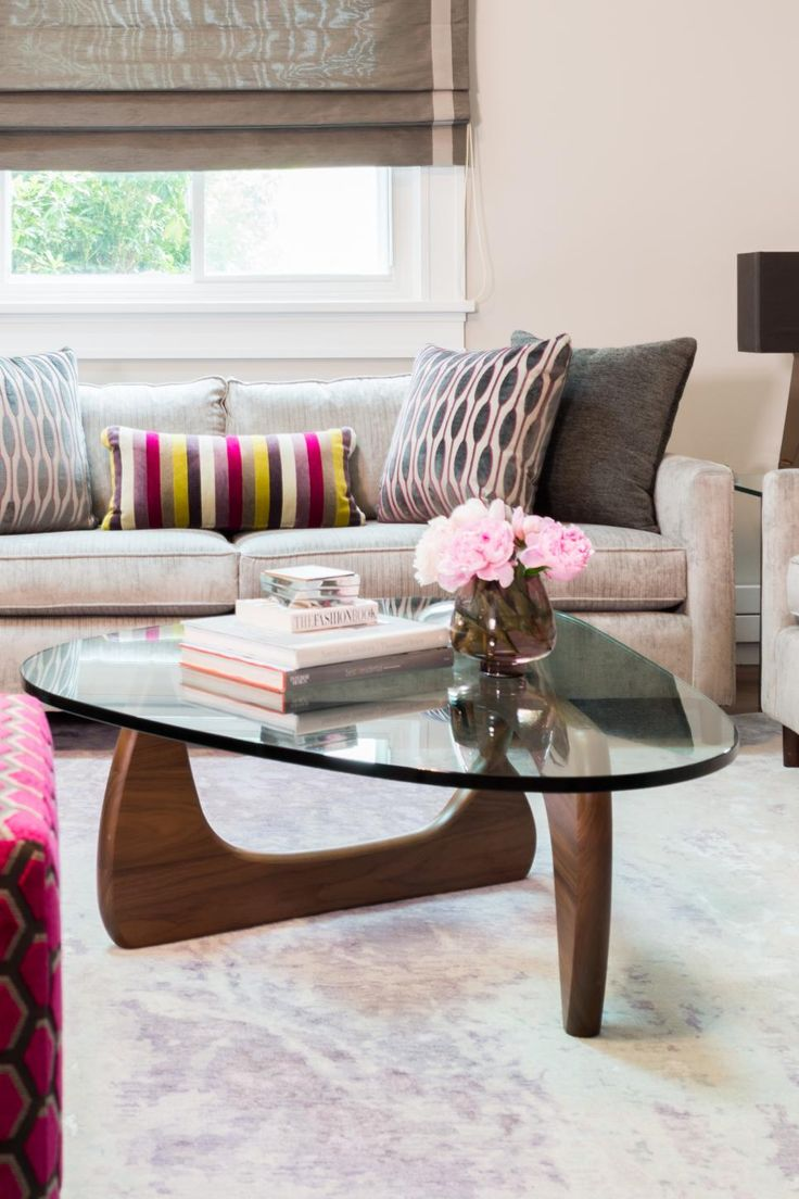 A midcentury modern glass coffee table creates the look of more space in this gorgeous sitting room, while a contemporary sofa and chair provides seating that is as comfortable as it is stylish.