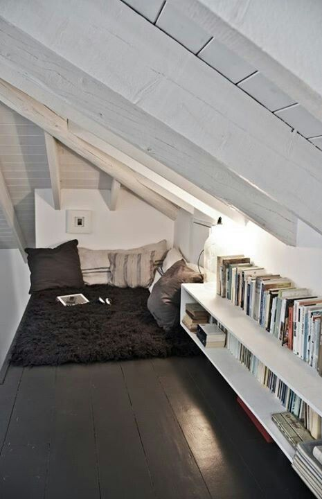 corner attic lounging area with throw pillows on floor and book shelves
