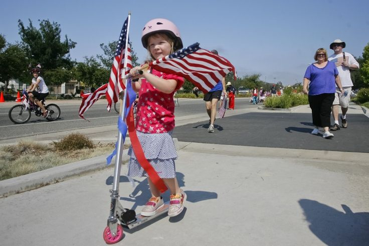 """""""Spreading Patriotic Pride"""" --   Fayth Hedlund, 4-yrs.-old, rides her scooter in the 3rd annual Miller Family YMCA July 4th Parade. [Source: Capture @ The Acorn Newspapers] -- #girls #children #females #people #parades #IndependenceDay #FourthofJuly #4thofJuly #JulyFourth #July4th #Scooters #AmericanFlags"""