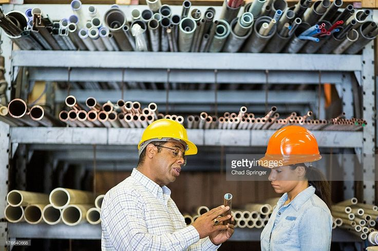 Stock Photo : Two warehouse workers looking at copper pipe