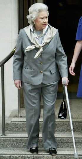 14 January 2003: The Queen leaves King Edward VII hospital in London with a cane after a knee operation. Rare photo of the Queen in pants.