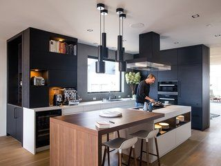 #kitchen | Domino Effect: How a Bedroom Refresh Jump-Started a Whole-House Remodel For a Tech Exec - Photo 9 of 14 - The black steel A110 pendants by Alvar Aalto match the Poliform ventilation hood and ebonized white oak cabinets by Leicht Haus. LED lighting is integrated into the island shelving. The drawers underneath are handleless and open electronically by touch using a servo drive.