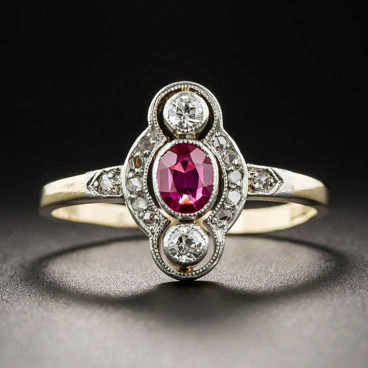 Delicately hand-fabricated in platinum over gold during the first or second decade of last century, this sweet petite and precious Edwardian jewel features a bright red oval Burmese ruby accompanied north and south by small collet-set European-cut diamonds. Tiny rose-cut diamonds twinkle on the sides and shoulders. 1/2 inch long, Currently ring size6 3/4.
