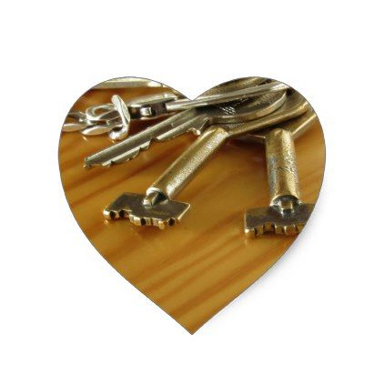 Bunch of worn house keys on wooden table heart sticker ...