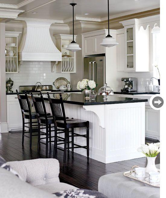 White flat panel cabinets, black countertops, dark wood floor, white tile backsplash, pendent lights over island crown molding?