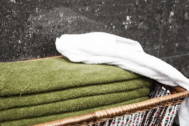 green towels and white towels well placed in a basket in the bathroom