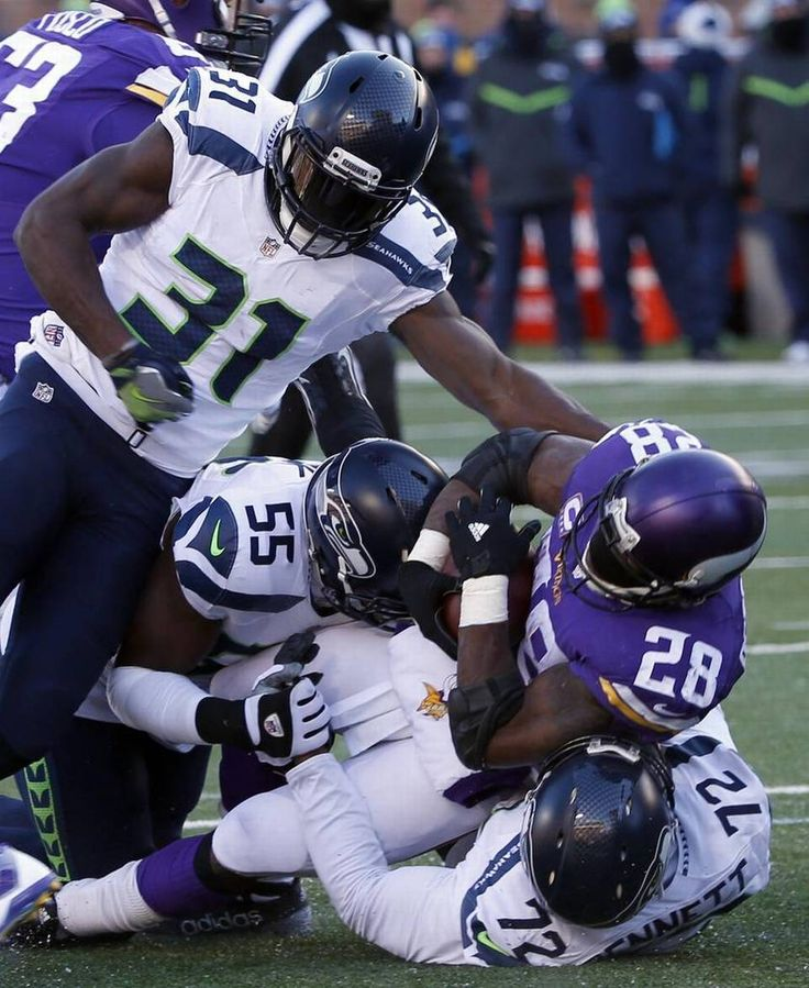 Seattle's Kam Chancellor (31), Frank Clark (55) and Michael Bennett (72) take down Minnesota's Adrian Peterson (28). The Seahawks limited Peterson to 45 yards rushing.