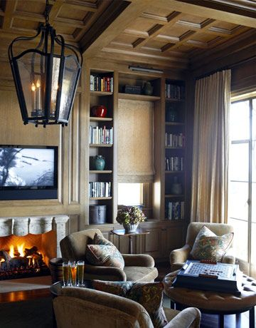 Wood Panneled Media Room.  This den designed by Joe Nye feels cozy but not oppressive and dark. The room was once a somber mahogany color, but Nye lighted it to a mellow café au lait. The view from this Santa Barbara home, looks out onto the ocean.