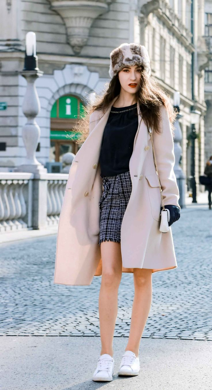 Fashion Blogger Veronika Lipar of Brunette from Wall Street wearing white sneakers from Diesel, black and white plaid tweed mini skirt from Storets, black silk blouse from Juicy Couture, off-white double breasted wool coat from MaxMara, faux fur headband, chain strap shoulder white bag, blue leather gloves walking down the street in Ljubljana