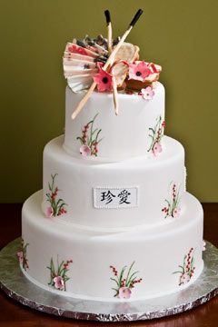 Round three tier white Asian style wedding cake with Asian fan and Chinese chop sticks wedding cake topper. The cake tiers a decorated with hand decorated floral work and a pink cherry blossom.