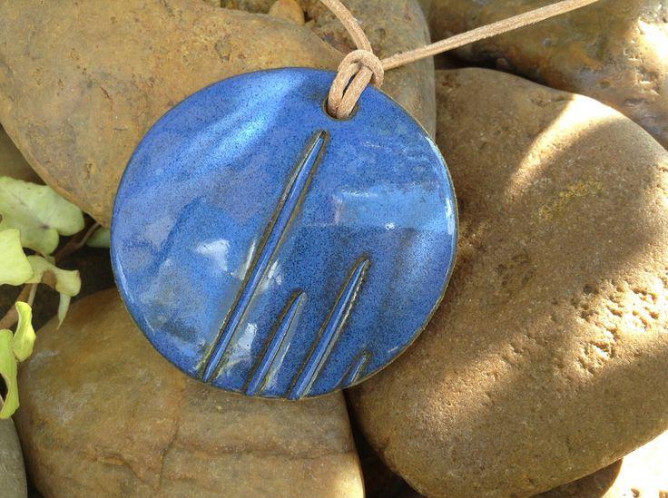 Colar exclusivo, longo, com pingente em cerâmica de alta temperatura, fio de couro natural de 2 mm, na cor natural. Os metais de acabamento são em prata de lei 925. <br>Por ser um produto artesanal, a peça poderá apresentar pequenas variações em sua forma, medidas e cores.