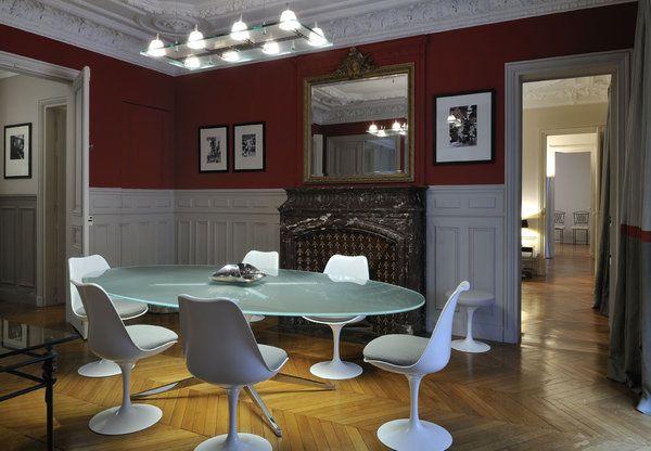 Dans la salle à manger chaises Tulip de Eero Saarinen et piètement de table vintage Knoll, surmonté d'un plateau en verre. On retrouve le rouge anglais des murs (peintures Flamant) en bande de rappel sur les rideaux.