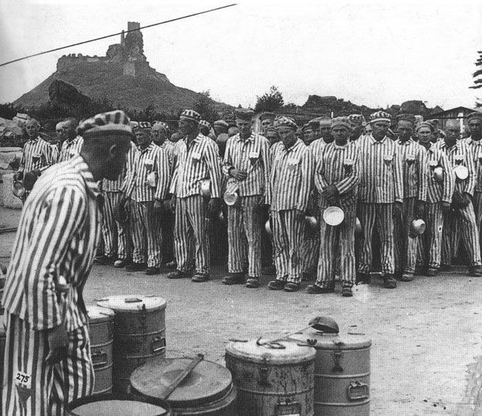 Distribution of food to prisoners in Flossenbürg. The prisoners, who were assigned to  the granite quarry, stood to attention before receiving a portion of food from the kapo. Germany, 1944.