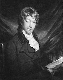 A young man with brown, curly hair sitting in front of some kind of cloth. Books can be seen underneath the cloth; the man is wearing a jacket with a white cravat