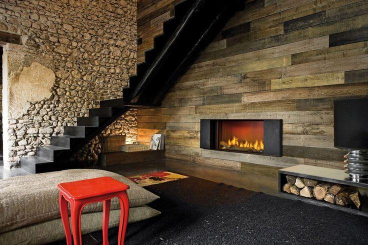 Ambiente che abbina vari stili tra rustico, moderno e minimal - camino aperto costruito all'interno di muro rivestito in legno