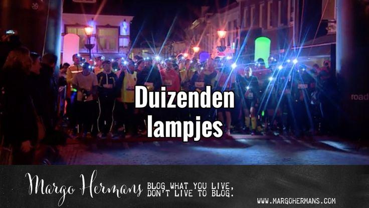 Een lint van duizenden lampjes trok door de donkere straten van de stad.