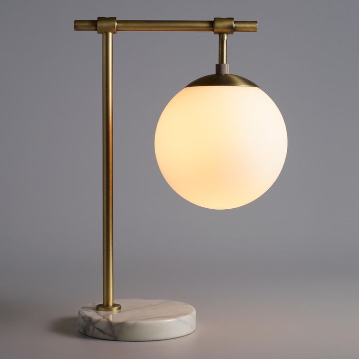 Add a mid-century modern look to your decor with our exclusive frosted glass task lamp. Crafted of matte brass with a real white marble base that lends it extra stability, it boasts an enclosed globe shade that filters light.