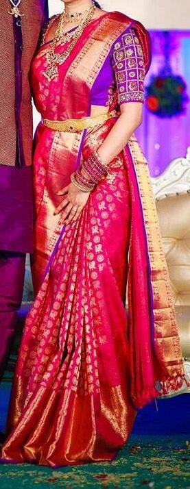 South Indian bride. Gold Indian bridal jewelry.Temple jewelry. Jhumkis. Pink silk kanchipuram sari with contrast embroidered purple blouse.Braid with fresh flowers. Tamil bride. Telugu bride. Kannada bride. Hindu bride. Malayalee bride.Kerala bride.South Indian wedding.