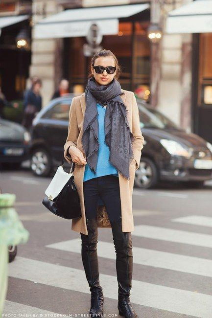 "Irina Shayk in blue shirt, black pants, and camel coat, accessorized with Chanel over-the-knee boots, Celine sunglasses, Louis Vuitton scarf, and Celine ""Trapeze"" bag."