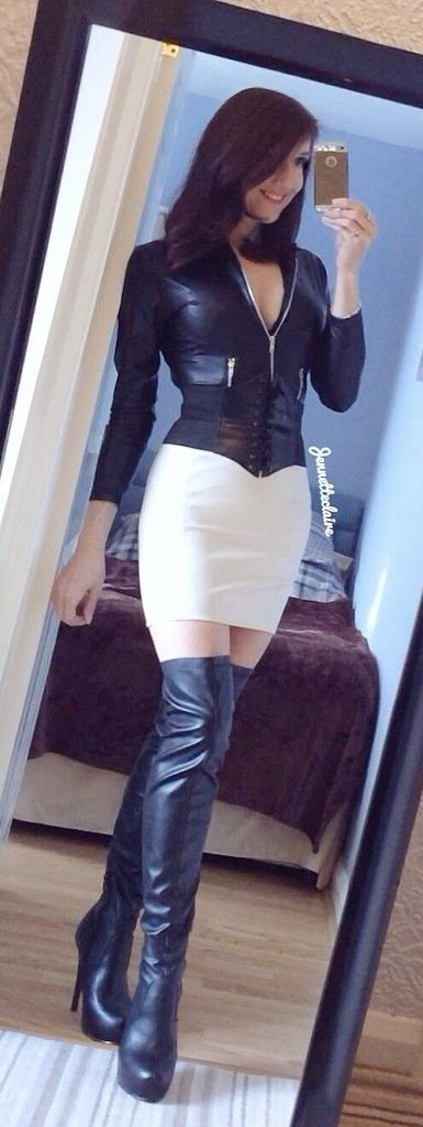 Sexy amateur bedroom selfie in leather top, white skirt, and black leather OTK boots