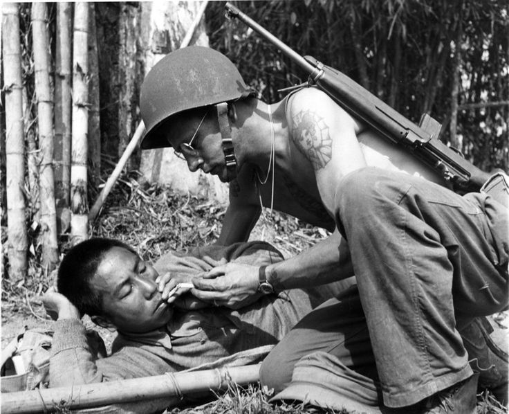 U.S. Army Pfc. Ralph G. Smith of Morristown, New Jersey lights a cigarette for a wounded Chinese ally during the fighting in the isolated Hukawng Valley when American and Chineseforcessucceeded in driving theJapaneseout ofnorthernBurma. Hukawng Valley, Myitkyina District, Kachin State, Burma (Myanmar).April 1944.