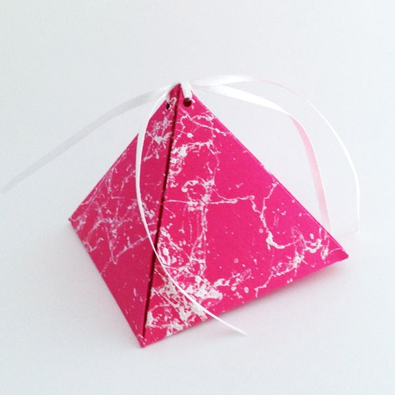 Hot pink paper was sprayed with white webbing and made into a triangle box.