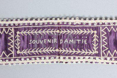 Embroidered silk garter, French, late 18th century. Purple satin embroidered in white chain stitch 'Souvenir d'Amite'.