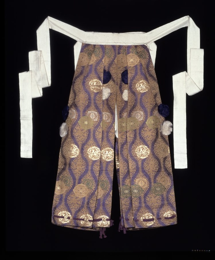 part of Samurai's two piece hitatare outfit woven in gold, violet, and green silk and unglossed silk threads with roundel of phoenixes and foliage on a design of stylised phoenix tails on a beige ground with tassels. Edo Period. British Museum.