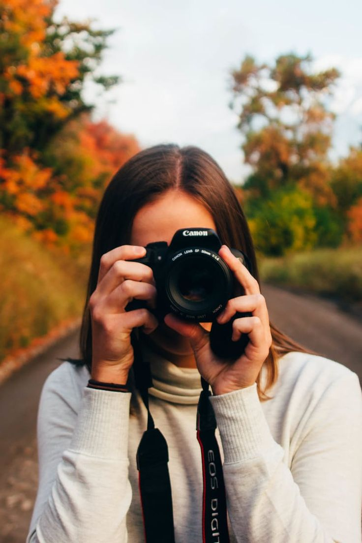 Woman in White Long Sleeve Shirt Taking Picture