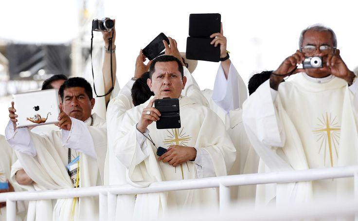 Priests take pictures as Pope Francis arrives to lead a mass at the Los Samanes park in Guayaquil, Ecuador. Pope Francis landed in Ecuador's capital Quito on Sunday to begin an eight-day tour of South America that will also include visits to Bolivia and Paraguay. Alessandro Bianchi.