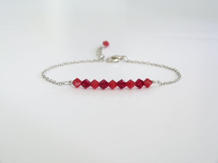 Bracelet rouge composé de toupies en cristal Swarovski et d'une chaîne en métal argenté : Bracelet par oana-bruz