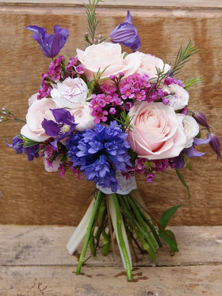 Spring pink and purple rustic hand-tied bridal bouquet of sweet avalanche roses, purple clematis, hyacinth, ranunculus, and waxflower complete with vintage lace to bind. Florissimo, Shropshire