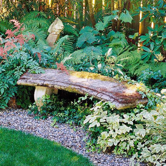 Curved bench in a shady garden border blends with its surroundings