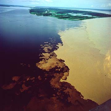 """Amazon """"Meeting of the Waters"""" Rio Negro and Rio Solimões meeting is the point at which the Rio Negro meets the Rio Solimões in the Brazilian state of Amazonas.Due to differences in temperature, speed and density, the two rivers' differently colored waters don't mix immediately, but flow side by side for several miles."""