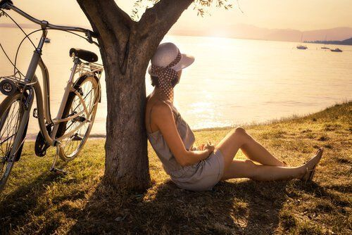 Mujer-solitaria-sentada-en-el-suelo-mirando-al-lago