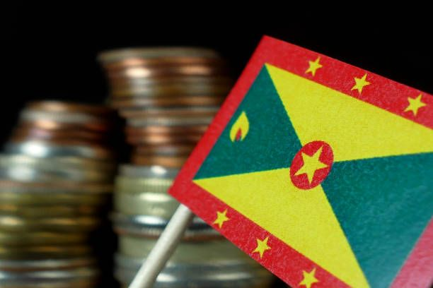 grenada flag waving with stack of money coins macro